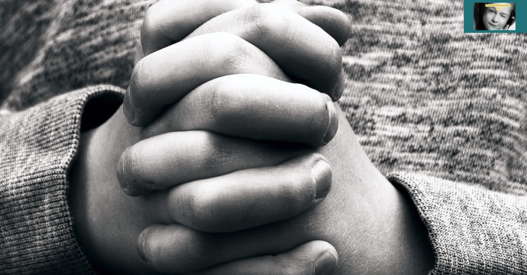 Child with hands clasped in prayer.