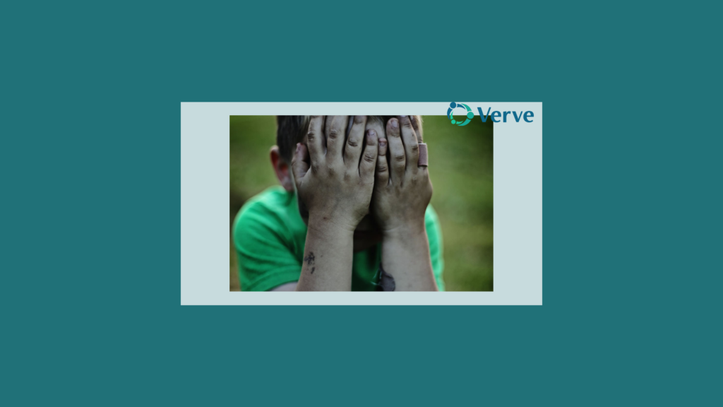 child with dirty hands covering his face