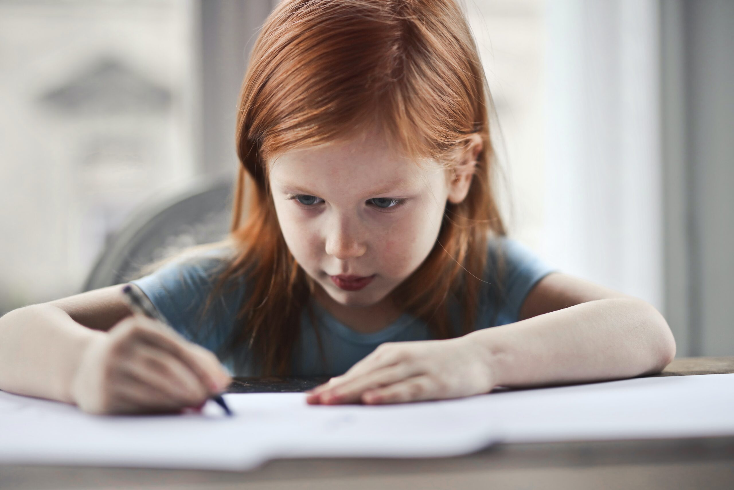 Little girl with red hair sitting alone writing in a book