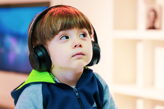 child alone with headphones on listening.