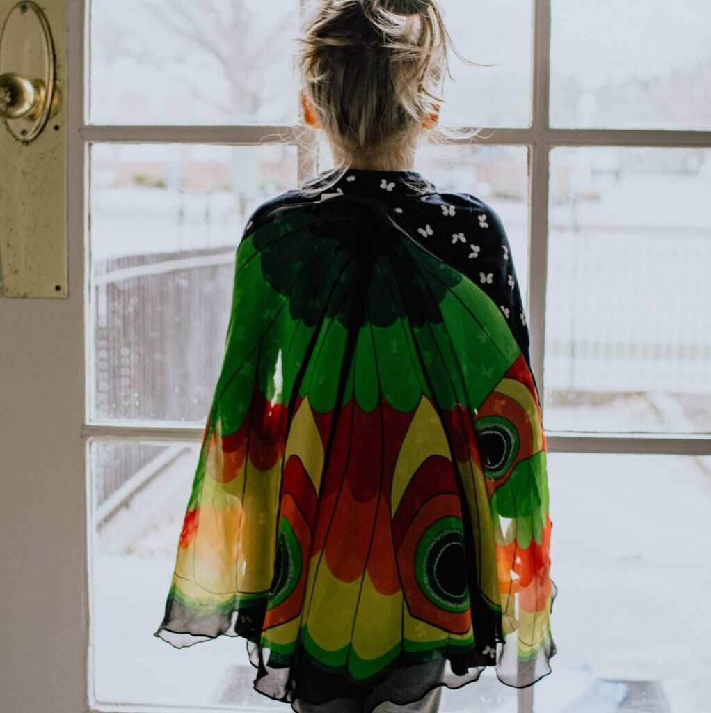child with a rainbow outfit looking through the window