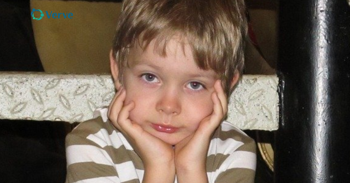 little boy sitting with his face in his hands looking moody
