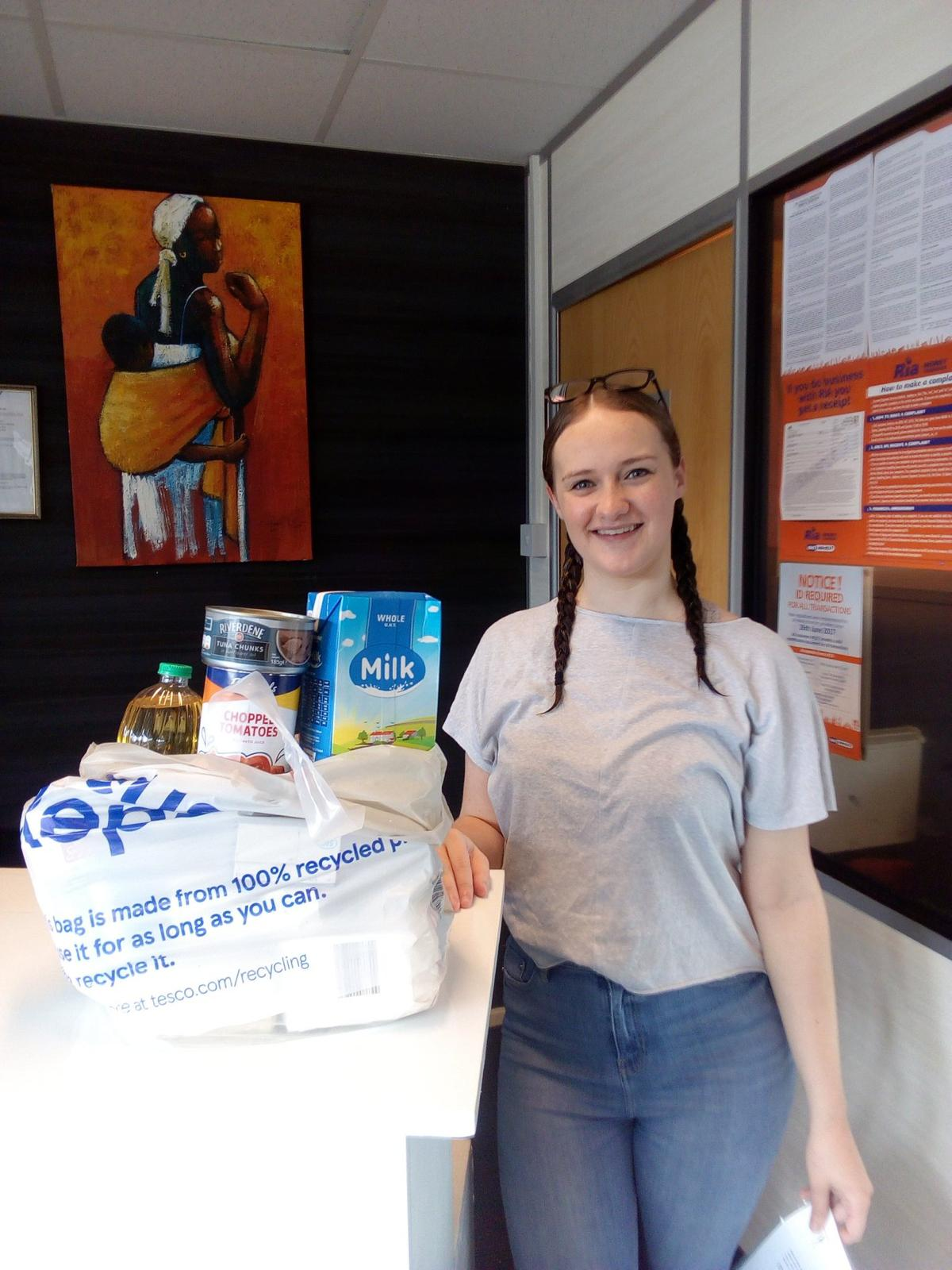 Young woman standing with a bag of food.