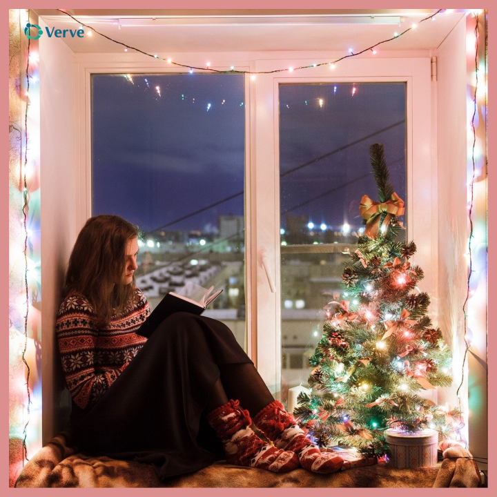 girl reading a book while sitting a window with a Christmas tree