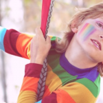 child on a swing with a rainbow jumper on wearing make up.