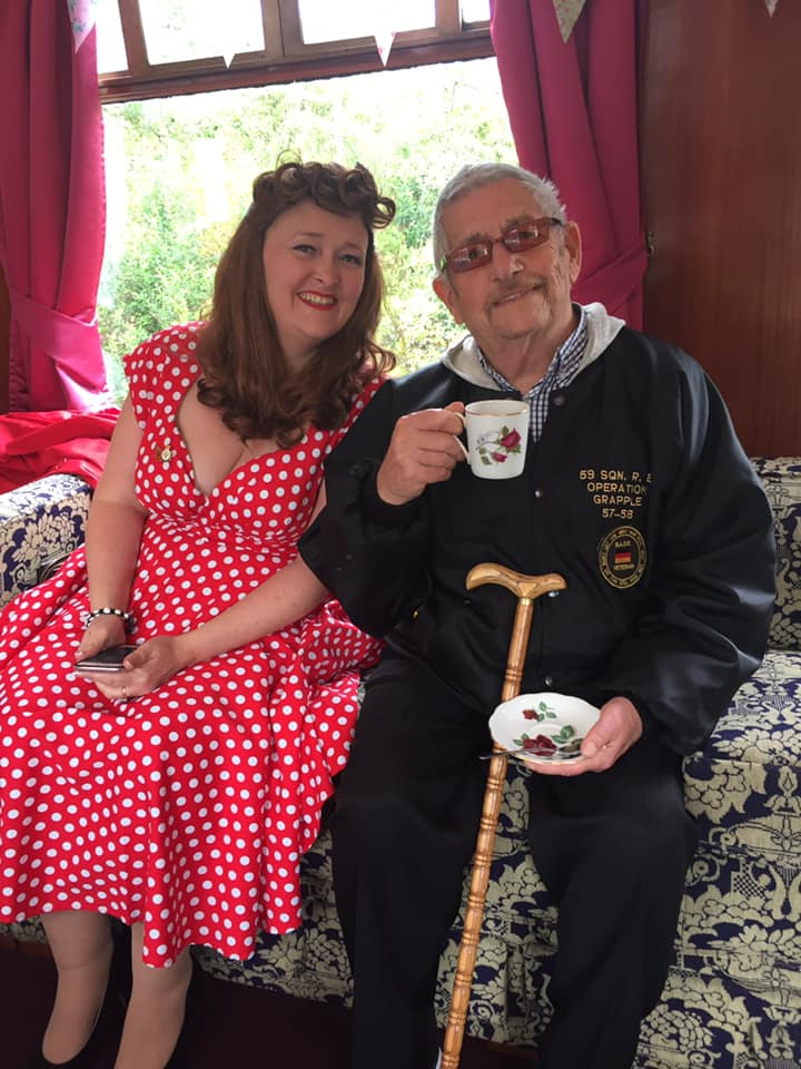 Woman and man having a cup of tea in 1940,s costume.