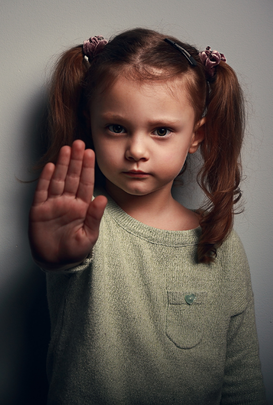 a young girl with her hand held towards the camera.