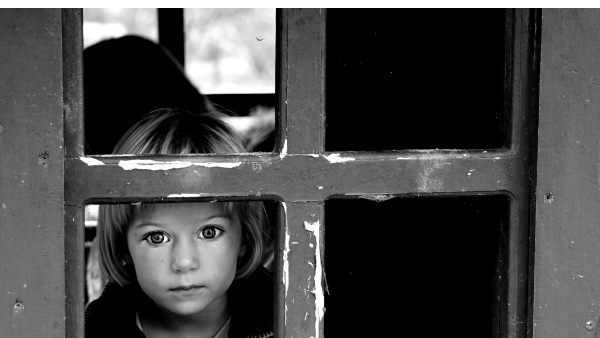 child in care looking through a window alone.